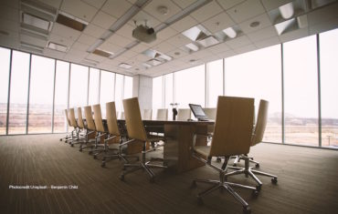 Ein Meetingtisch steht in der Mitte eines großen Büroraums. Darum herum sind weiße Bürostühle gestellt.