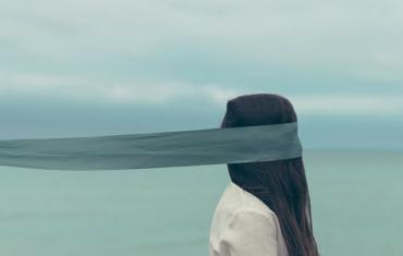 Eine Frau hat ein Tuch um den Kopf dessen Ende gehalten wird.