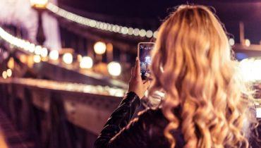 Blondes Mädchen fotografiert in der Nacht mit ihrem Smartphone eine erleuchtete Brücke