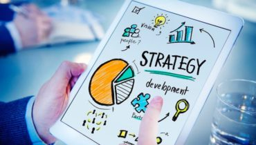 Ein Mann hält ein Tablett in der Hand auf dem eine Strategie mit Bildern dargestellt ist.