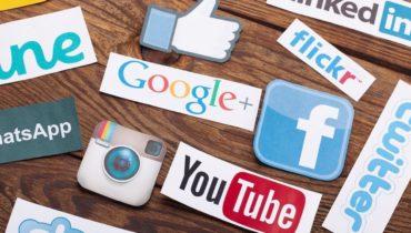 Ein Holztisch auf dem die Logos der sozialen Netzwerke verstreut liegen