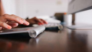 Finger auf einer zweigeteilten Tastatur, die gerade tippen.