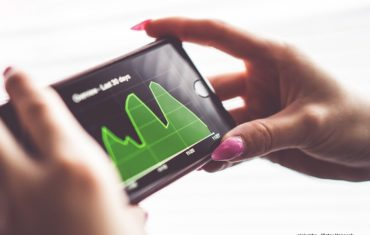 Frauenhänge halten ein Smartphone in der Hand auf dem eine Grafik zu sehen ist.