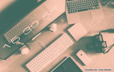 Computerbildschirm, Tastatur, Maus, Laptop und Kamera auf einem Schreibtisch