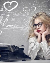 Blonde Frau mit zerstausten Haaren schaut auf eine alte Schreibmaschine und hat viele Gedanken im Kopf, die um sie herum schwirren.