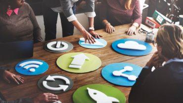 Mehrere Menschen stehen um einen Tisch und sitzen darum herum, um sich zu besprechen. Darauf Symbole für Rss-Feed, Teilen von Inhalten und einer Cloud.