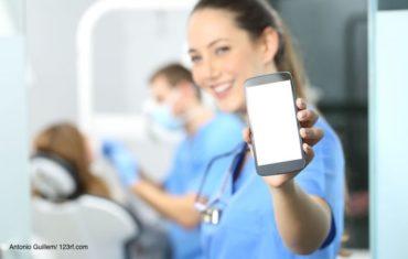 Zahnarzthelferin in einer blauen Uniform hält ein Smartphone in ihrer Hand nach vorne in die Kamera