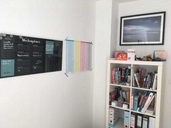 Glasmemoboard neben einem bunten Kalender an der Wand.