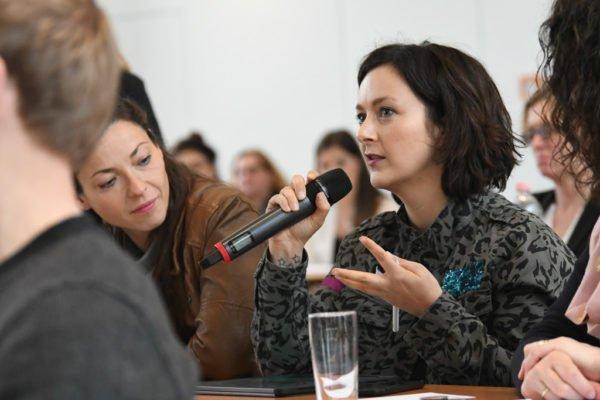 Frau hält ein Mikrofon und spricht
