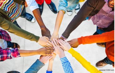 Arme sind in der Mitte des Bildes und die Hände legen sich übereinander. Die Arme haben verschiedene Hautfarben und beschreiben einen Zusammenhalt als Community.