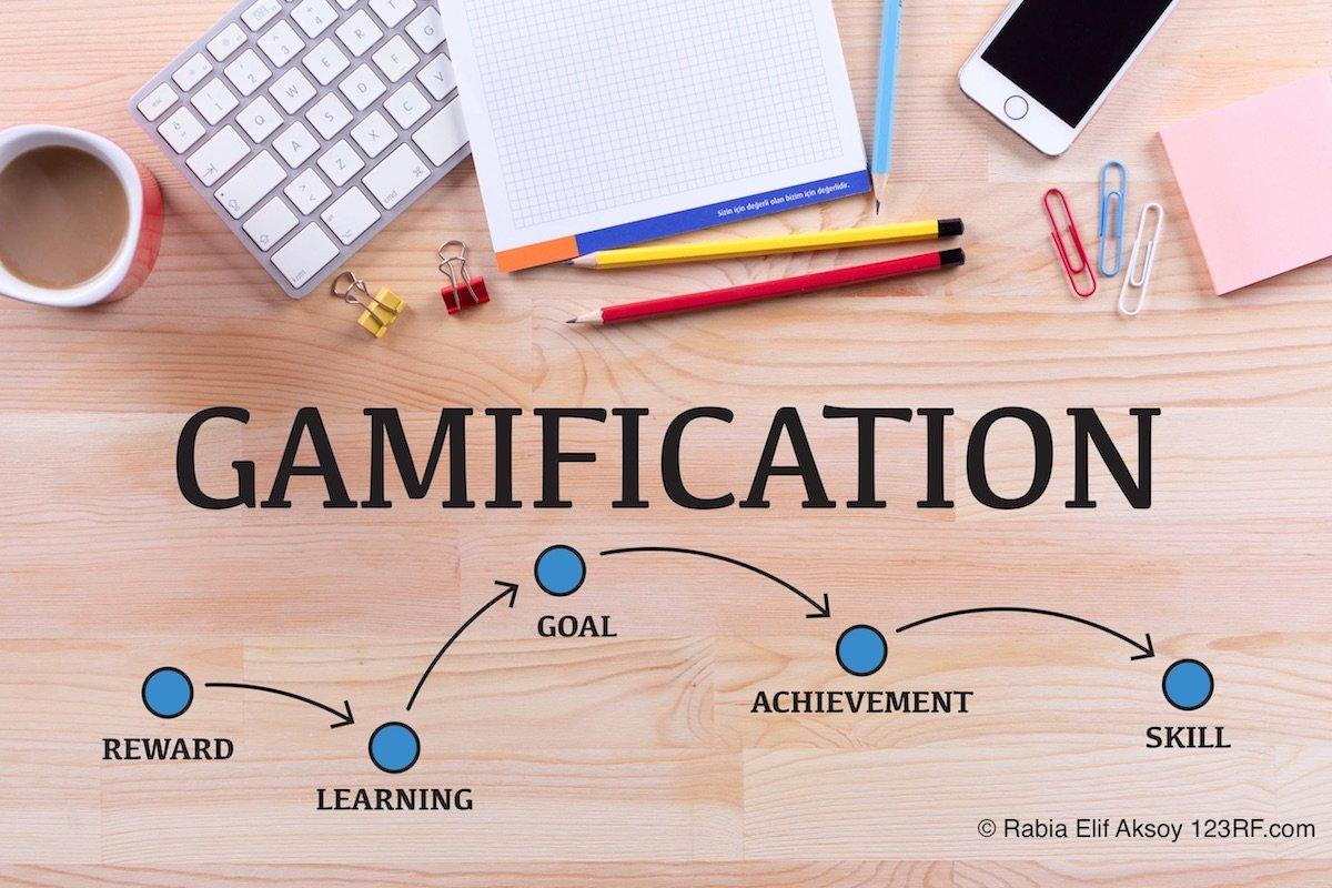 Holzplatte auf dem einen Tastatur liegt, ein Block, bute Stifte und ein Iohone. Darunter steht Gamification und Pfeile zeigen auf Reward, Learning, Goal, Achievement und Skill.