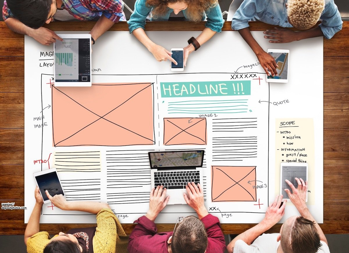 Mehrerer Personen sitzen mit mobilen Endgeräten um einen Tisch. Auf dem Tisch liegt ein großes Blatt Papier für die Magazin- und Blogplanung.